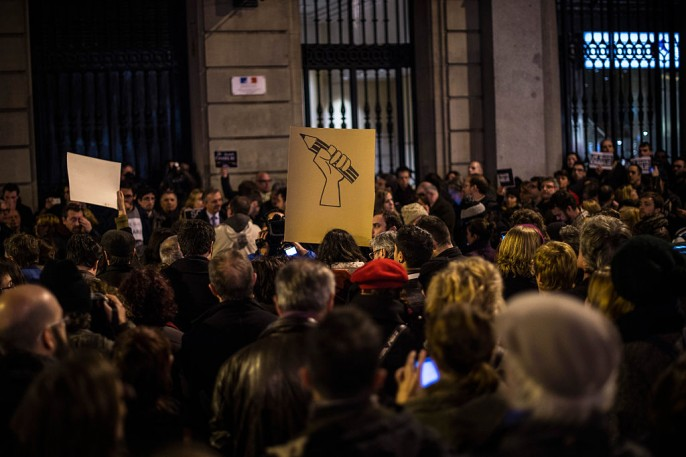 A woman holds a banner with a pencil painted during a gathering of people showing their support for the victims of the terrorist attack at French magazine Charlie Hebdo, in front of the Consulate of France on January 7, 2015 in Barcelona, Spain.