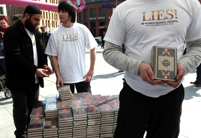 "Muslims wait for pedestrians to take copies of the Koran at Potsdamer Platz in Berlin, Germany. The phrase ""LIES,"" the German slogan of the group distributing the Korans, translates as the imperative ""READ"" in English. Islamic radicals in Germany have launched an unprecedented nationwide campaign to distribute 25 million copies of the Koran, translated into the German language, with the goal of placing one Koran into every household in Germany, free of charge. The group, which calls itself 'The True Religion,' claims that 300,000 copies have already been distributed. German officials have raised serious concerns about the initiative, calling it an abuse of the holy text."