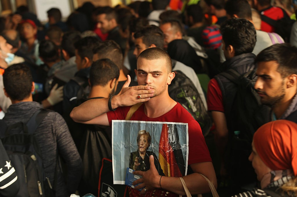 A migrant from Syria holds a picture of German Chancellor Angela Merkel as he and approximately 800 others arrive from Hungary at Munich Hauptbahnhof main railway station on September 5, 2015 in Munich, Germany. Thousands of migrants are traveling to Germany following an arduous ordeal in Hungary that resulted in thousands walking on foot and then being bussed by Hungarian authorities from Budapest to the Austrian-Hungarian border.