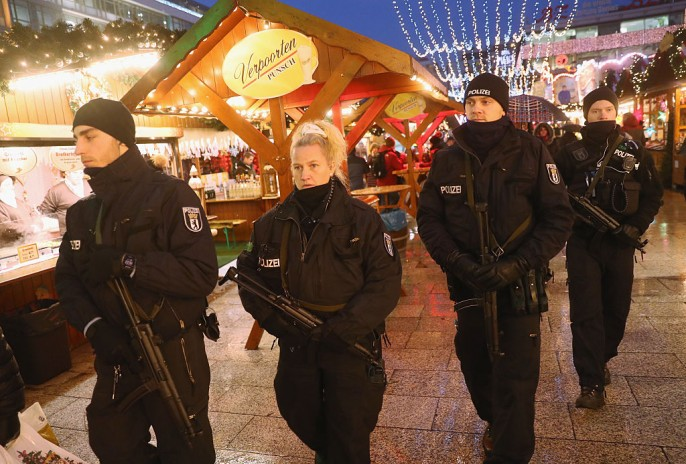 Heavily-armed police walk through the reopened Breitscheidplatz Christmas market where three days ago a truck plowed into the market, killed 12 people and injured dozens in a terrorist attack on December 22, 2016 in Berlin.